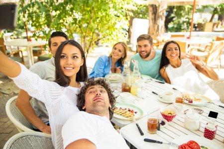 Photo pour Portrait d'un heureux amis faisant selfie photo dans un restaurant en plein air - image libre de droit