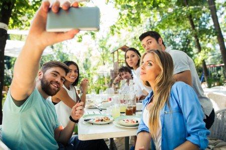 Friends making selfie photo in outdoor restaurant