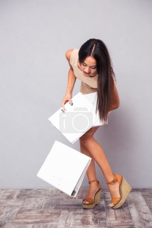 Businesswoman dropping folders on the floor