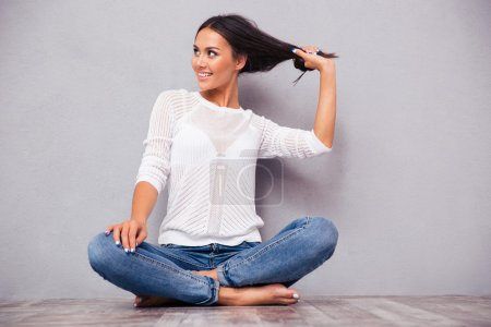 Woman in jeans sitting on the floor