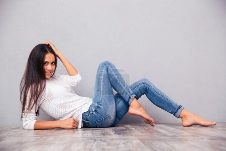 Photo for Portrait of a smiling attractive woman lying on the floor on gray background - Royalty Free Image