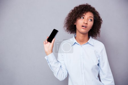 Bored afro american woman holding smartphone