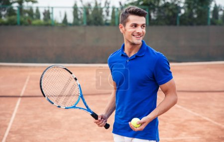 Happy man playing in tennis outdoors