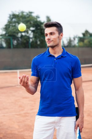 Male tennis player standing outdoors