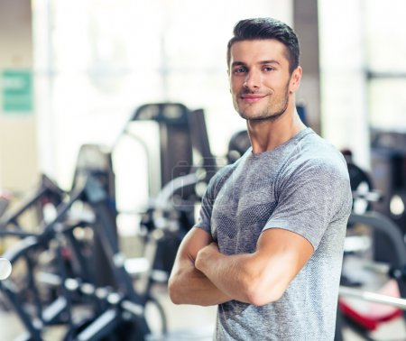 Photo for Portrait of a happy fitness man standing with arms folded at gym and looking at camera - Royalty Free Image