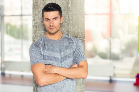 Photo for Portrait of a fitness man standing with arms folded in gym and looking at camera - Royalty Free Image