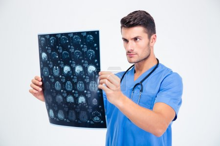 Male doctor looking at x-ray picture of brain