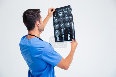 Back view portrait of a male doctor looking at x-ray picture