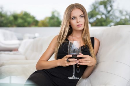 Woman drinking red wine in restaurant