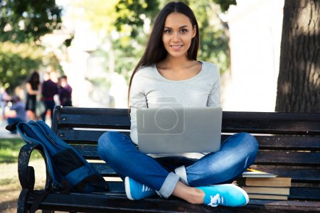 Female student sitting on the bench with laptop