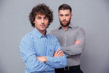 Photo pour Portrait de l'un deux entrepreneurs occasionnels grave debout avec les bras croisés sur fond gris - image libre de droit