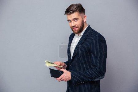 Photo pour Portrait d'un riche homme d'affaires tenant de l'argent sur fond gris et regardant la caméra - image libre de droit