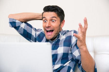 Excited man sitting on the sofa with laptop