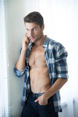 Photo for Portrait of a young man with perfect body talking on the phone and looking in window at home - Royalty Free Image