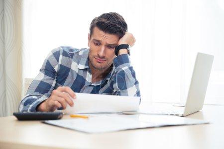 Photo pour Portrait d'un homme triste regardant les factures à la maison - image libre de droit