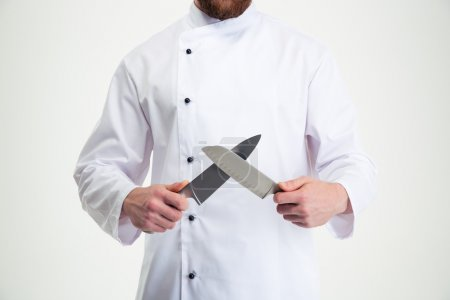 Photo for Closeup portrait of a male chef cook sharpening knife isolated on a white background - Royalty Free Image
