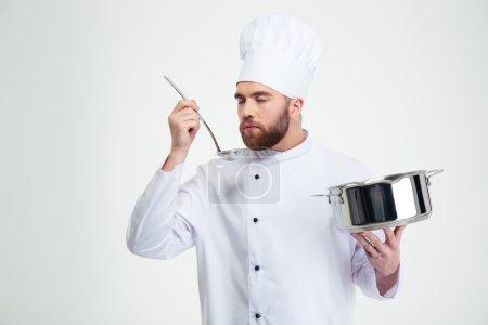 Photo pour Portrait d'un cuisinier homme tenant une casserole et une louche isolées sur un fond blanc - image libre de droit