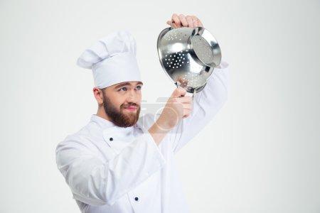 Photo pour Portrait d'un chef cuisinier tenant une passoire isolée sur fond blanc - image libre de droit