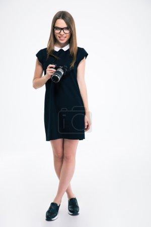 Photo pour Portrait de toute la longueur de la souriante jeune femme debout avec caméra isolé sur fond blanc - image libre de droit