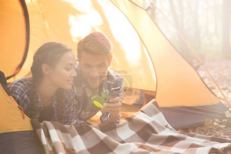 Couple using smartphone in the tent