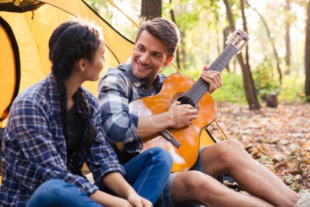 Couple sitting with guitar in the forest