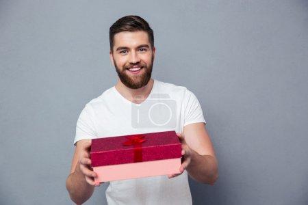 Photo pour Portrait d'un homme heureux donnant boîte cadeau sur appareil photo sur fond gris - image libre de droit