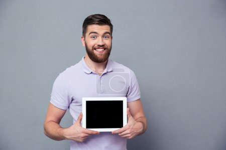 Smiling man showing blank tablet computer screen