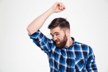 Portrait of a casual man smelling his armpit