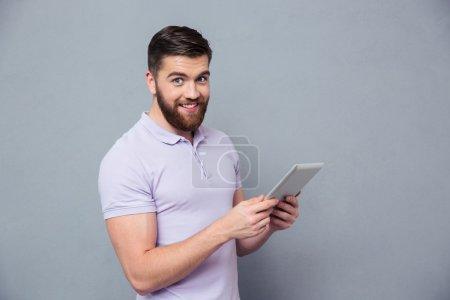 Photo pour Portrait d'un homme souriant décontracté tenant un ordinateur tablette et regardant la caméra sur fond gris - image libre de droit