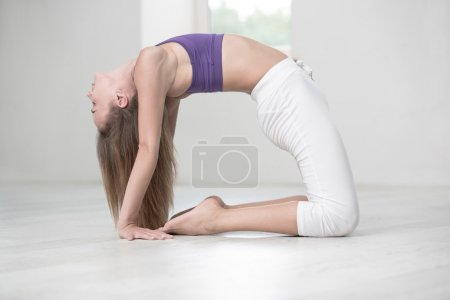 Woman doing yoga exercises in gym