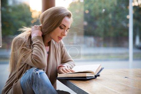 Photo pour Portrait d'une belle fille livre de lecture dans un café - image libre de droit