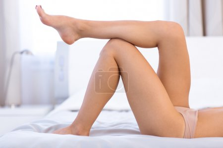 Sexy female legs on the bed