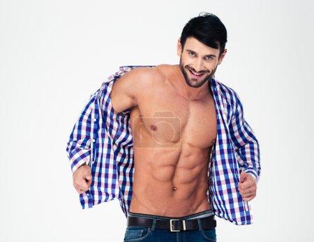 Smiling muscular man undressing shirt
