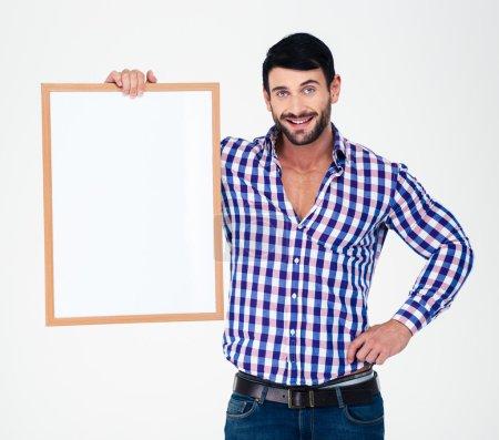 Photo pour Portrait d'un jeune homme heureux tenant un tableau blanc isolé sur un fond blanc - image libre de droit