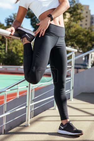 Woman stretching legs outdoors on the stadium