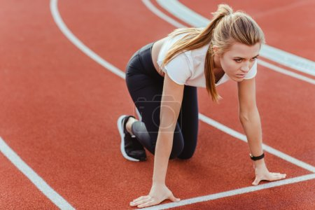 Photo for Portrait of female runner standing in start position at stadium - Royalty Free Image