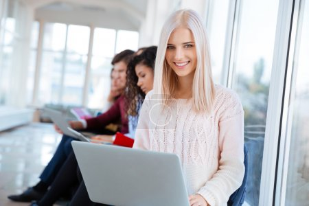 Woman sitting with laptop in university campus