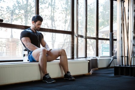 Fitness man listening to music sitting on windowcill
