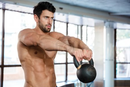 Muscular man workout with kettle ball