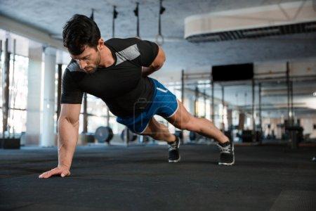 Athlet doing one hand push-ups