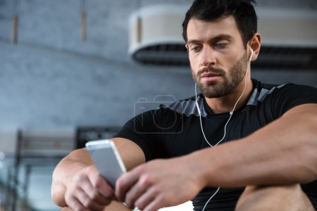 Sportsman using cellphone and listening to music