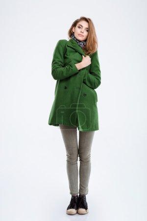 Photo pour Portrait d'une belle jeune femme en manteau permanent isolé sur fond blanc et à la recherche à la caméra - image libre de droit