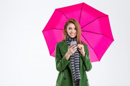 Woman holding smartphone under umbrella