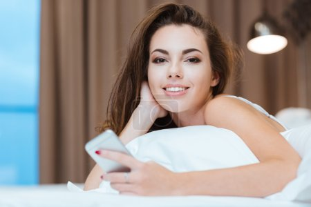 Woman lying on the bed with smartphone