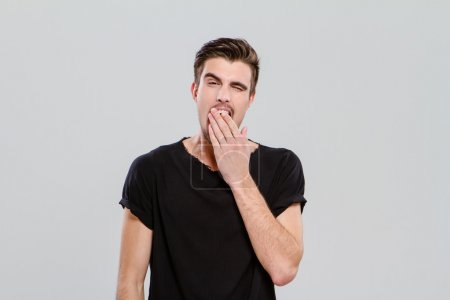 Exhausted young guy yawning and closing mouth by hand