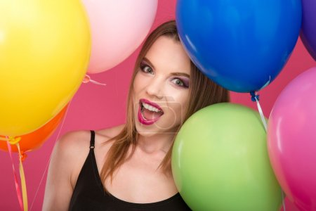 Closeup of excited glamour young female with colorful balloons