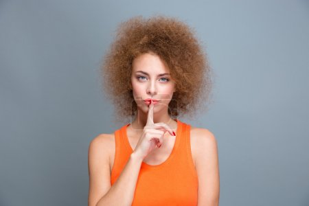 Beautiful curly woman showing silence sign