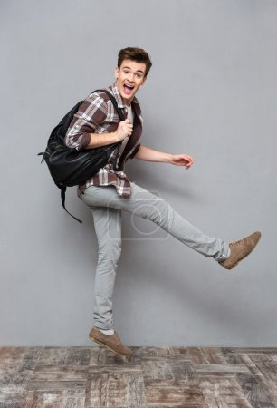 Funny cheerful male student jumping