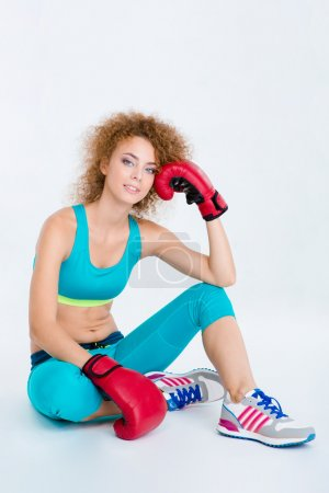 Photo for Portrait of a happy sports woman in boxing gloves sitting on the floor isolated on a white background - Royalty Free Image