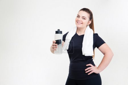Smiling thick woman in sportswear holding shaker